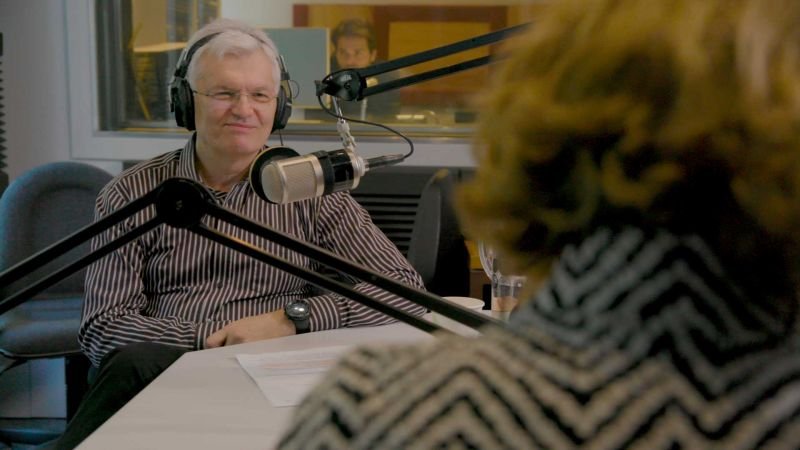 A man sitting in front of a microphone in a studio being interviewed