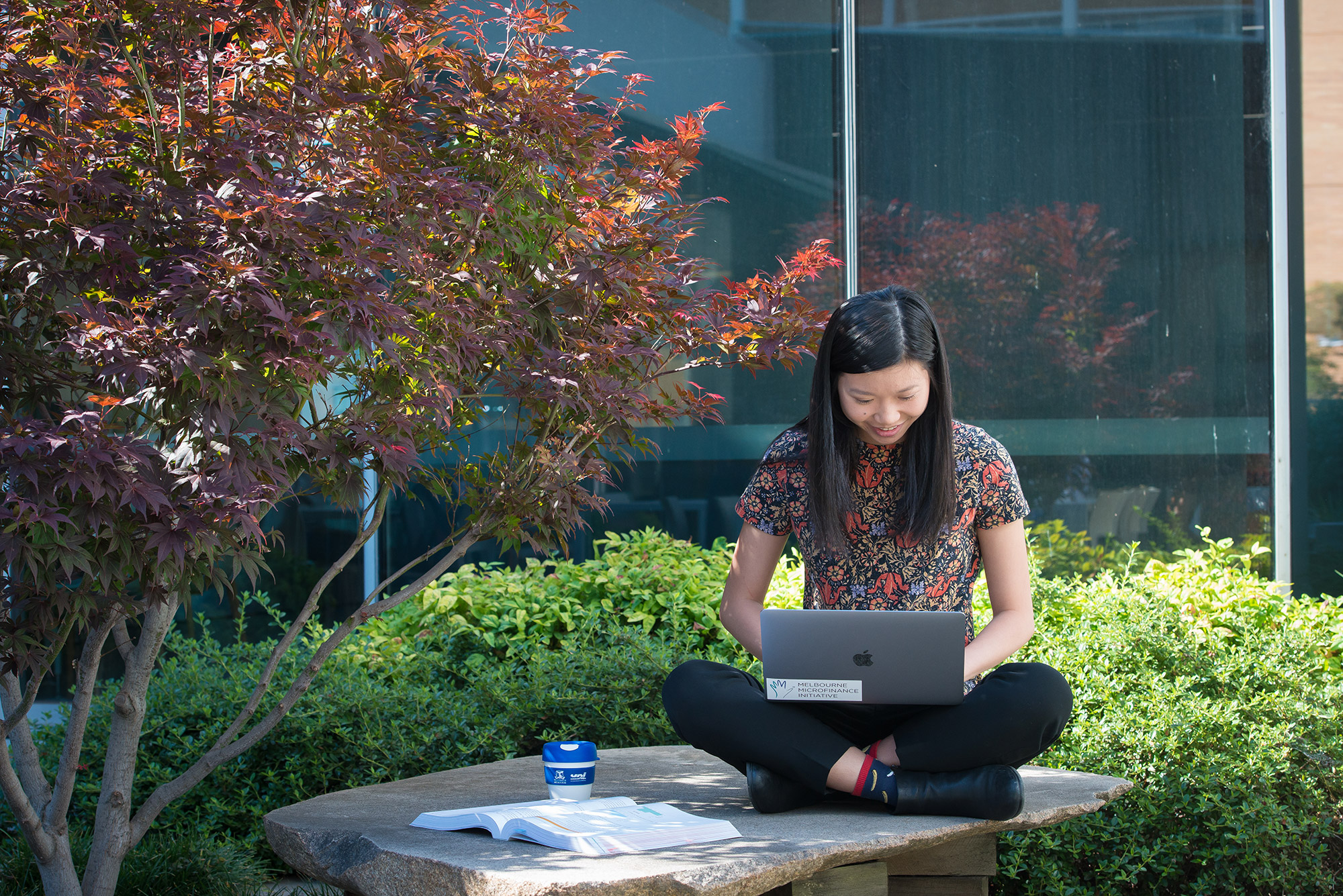 Female student sitting outside working on a laptop