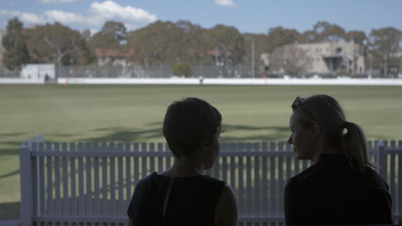 two people sitting by a sports oval