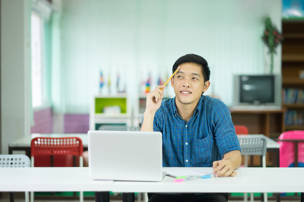 Student at laptop thinking