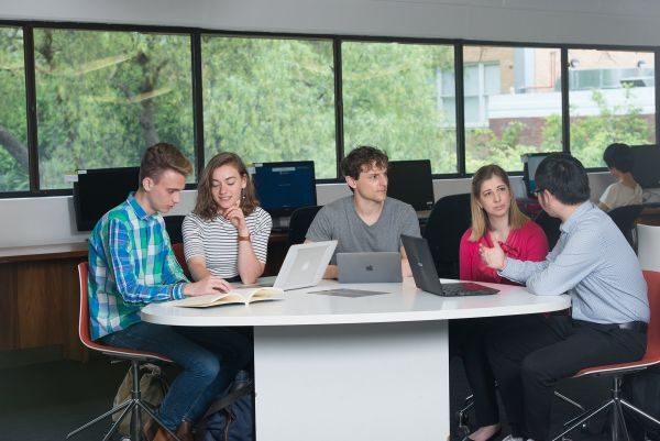 Five students sitting around a table with laptops talking