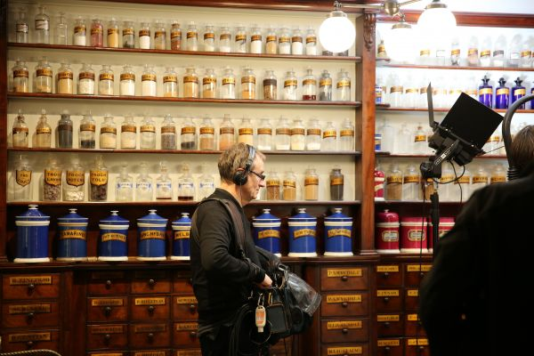 Sound recordist in front of shelves of jars