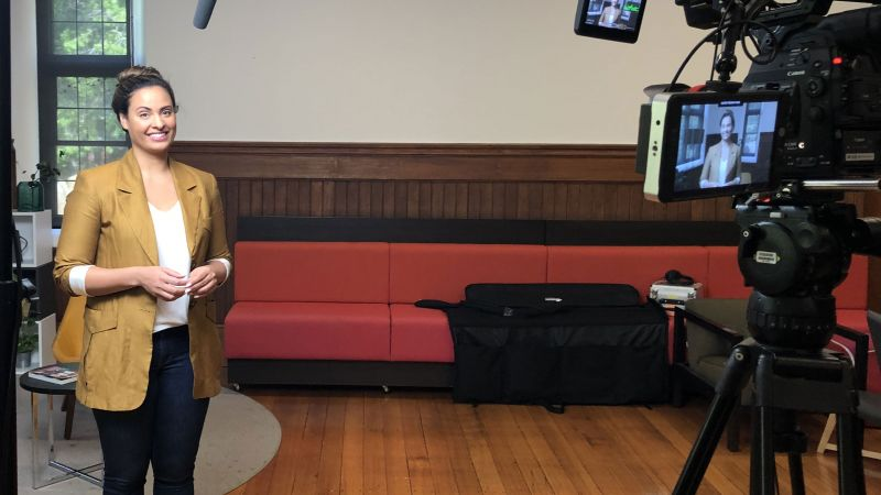 Person smiling in front of a video camera